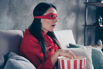 Close up side profile photo beautiful she her superpower lady costume hold popcorn container watch premiere new long wait comics picture wear red eye mask mantle sit sofa couch divan house indoors