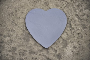 Heart made of graphite slate on a stone background.
