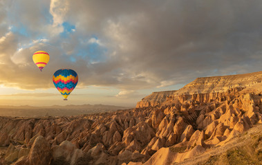 Panoramic view of geological rock formations and hot air balloons in Cappadocia Region, Turkey