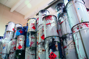 A collection of paint cans, glue buckets, mastic and toxic and hazardous material stacked