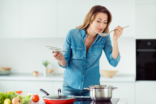 Portrait of her she nice lovely attractive dreamy brown-haired lady smelling tasting new fresh recipe dish meal snack dinner lunch household in light white interior style kitchen
