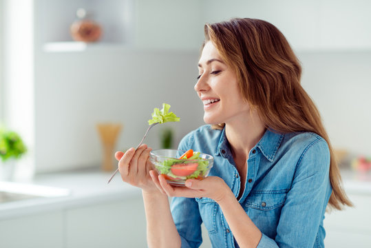 Close-up portrait of her she nice-looking sweet lovely charming cute attractive cheerful cheery positive brown-haired lady tasting new salad mix farm vegs in light white interior style kitchen