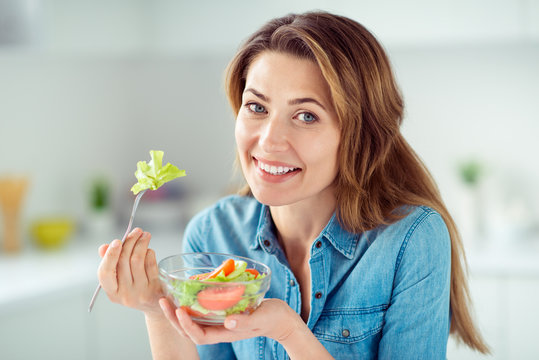 Close-up portrait of her she nice-looking lovely charming cute attractive shine cheerful cheery positive brown-haired lady tasting detox vitamin salad in light white interior style kitchen