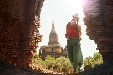 woman traveller with backpack walking through the Bagan looking the ancient ruins. Myanmar.