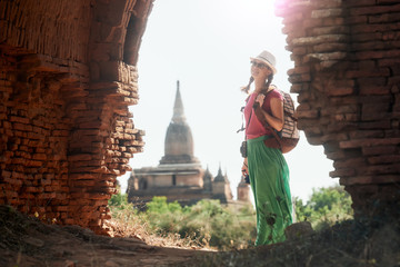 woman traveller with backpack walking through the Old Bagan looking the ancient ruins. Myanmar.