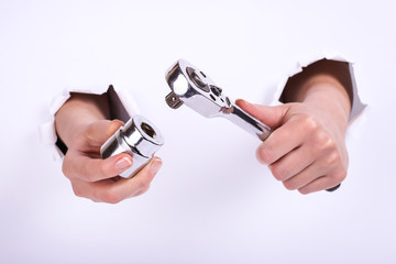 Ratchet wrench in a hand of the girl. Symbol of hard work, feminism and labor day. Isolate on white background.