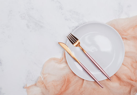 Empty white plate and modern design cutlery on the white marble table
