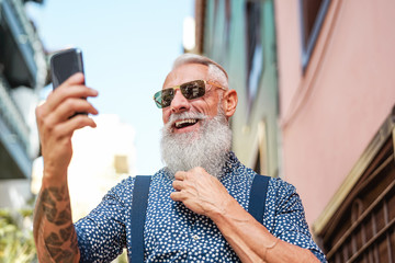 Bearded senior using mobile phone outdoor - Hipster mature man having fun with new trends smartphone apps - People lifestyle, technology and social influencer concept