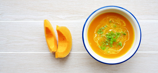 Pumpkin soup in white bowl with cream and parsley. Light wooden background