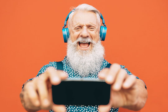 Senior bearded man making selfie with mobile phone while listening to his favorite playlist with headphones - Fashion matured male having fun with smartphone apps outdoor - Elderly, technology concept