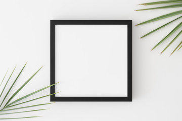 Top view of a black square frame mockup with palm leaf decoration.