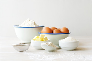 Ingredients for making dough, dessert on white wooden table. Flour, butter, sugar, eggs ingredients