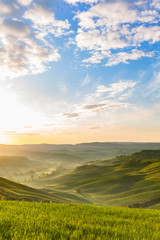Sunrise in the rolling hills with mist in the valley