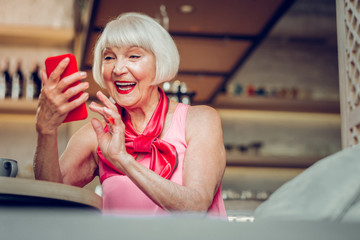 Delighted aged woman using her modern gadget