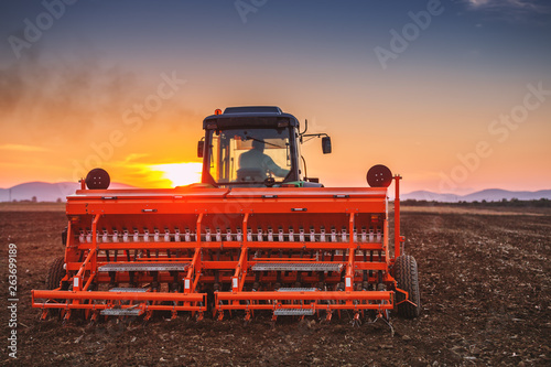 Wall mural Beautiful sunset, farmer in tractor preparing land with seedbed cultivator