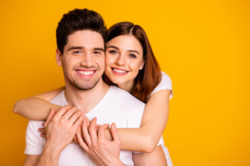 Close-up portrait of his he her she two nice cute lovely charming sweet tender attractive cheerful positive people cuddling isolated over vivid shine bright yellow background