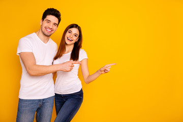 Close up photo beautiful she her he him his pair wondered direct indicate fingers empty space sale discount great little low price wear casual jeans denim white t-shirts isolated yellow background