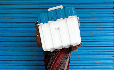 An election official carries Voter Verifiable Paper Audit Trail (VVPAT) machine at a distribution centre ahead of third phase of general elections in Kochi