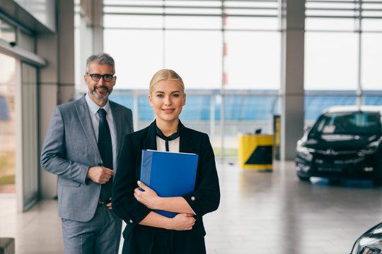 saleswoman and sales man in car dealership showroom