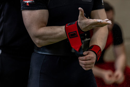 white caucasian man fixing his red wrist straps before lifting weights