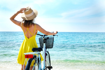 Young carefree woman in bright yellow dress with bicycle at ocean beach. Unrecognizable female...