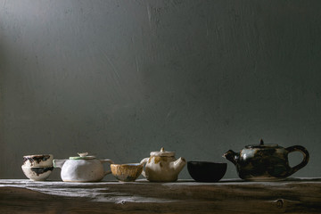Variety of craft handmade ceramic teapots and cups for tea ceremony standing on old wooden shelf in dark room.