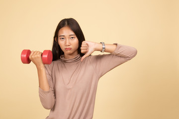 Unhappy Asian woman thumbs down with dumbbells.