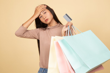 Unhappy  young Asian woman with shopping bags and credit card.