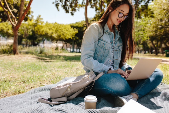 Student using laptop sitting in college campus