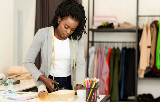 Fashion designer working in studio, cutting drawing