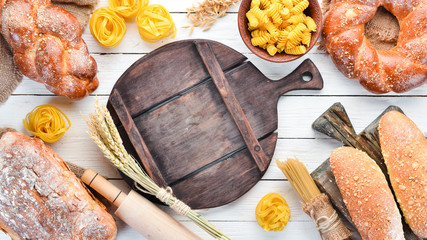 Wall Mural - Gluten free food. Various pasta, bread, snacks and flour on a white wooden background. Top view. Free space for your text.