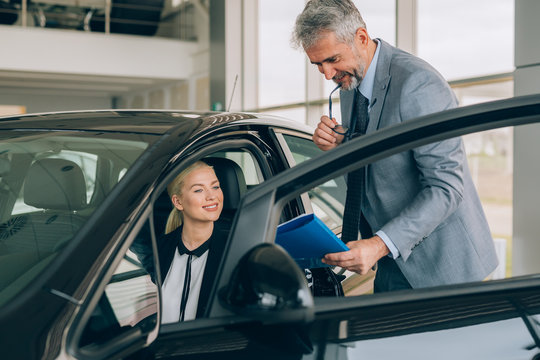 Salesman at the dealership showroom talking with customer and helping him to choose a new car