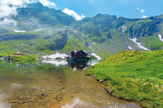 beautiful summer scenery around balea lake. grassy meadows and rocky ridge around. popular travel destination. location fagaras mountains, romania, europe. wonderful sunny weather