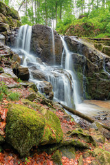 beautiful waterfall in the beech forest. huge mossy wet rocks. wonderful nature background. long exposure