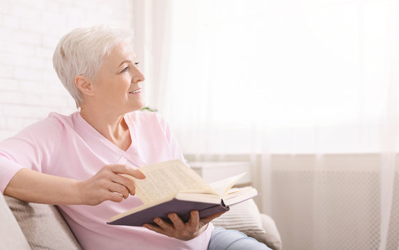Dreamy senior woman relaxing at home with favorite book