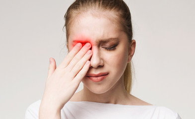 Upset woman suffering from strong eye pain