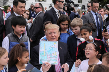 U.S. President Trump holds up colored in picture as he attends the 2019 White House Easter Egg Roll in Washington