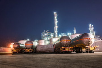 The oil truck tankers in the refinery background in the evening