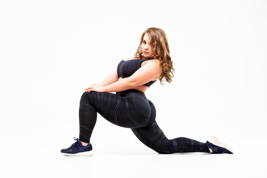 Plus size model in sportswear, fat woman doing workout on white background, body positive concept