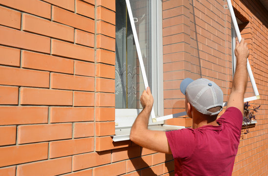 Mosquito wire screen installation. Worker installing mosquito wire screen on house window to protect from insects.