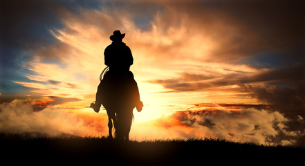 Cowboy on a horse at sunset Wall mural