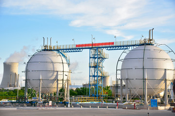 Refinery storage tanks and containers of ethanol under the blue sky white clouds