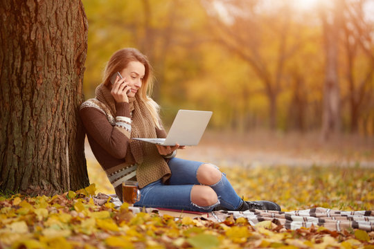 Beautiful girl sitting on a plaid in the fall leaves in the park, drinking hot tea and working on a laptop. Concept of autumn warmth, atmosphere and comfort, working in nature, freelancing, learning