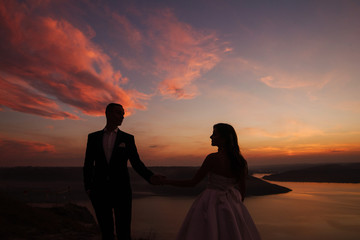 Romantic wedding couple of groom and bride in white dress walking holding hands on the hill near the beautiful lake. Scenic landscape view with sunset. Silhouette