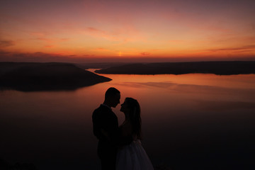 Silhouette of romantic wedding couple of groom and bride standing on the hill near the beautiful lake. Scenic landscape view with sunset. Bakota, Ukraine