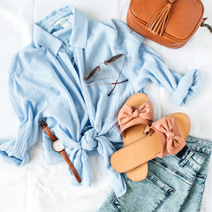 Feminine summer fashion composition with blouse, slippers, purse, sunglasses, watch, jean shorts on white background. Flat lay, top view minimalist clothes collage. Female fashion blog.