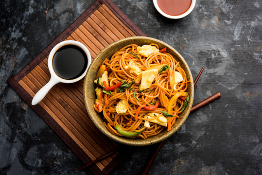 Egg Schezwan/hakka noodles, popular indochinese food served in a bowl with chopsticks. selective focus