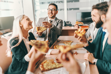 Small group of happy colleagues in formal wear chatting and eating pizza together for lunch. Talent...