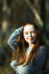 Portrait of cute teen girl with long bright red hair outdoors.