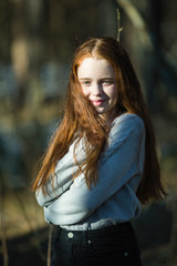Portrait of pretty young girl with long bright red hair outdoors.